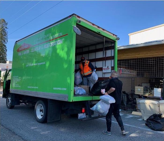 Men loading SERVPRO truck with bagged items