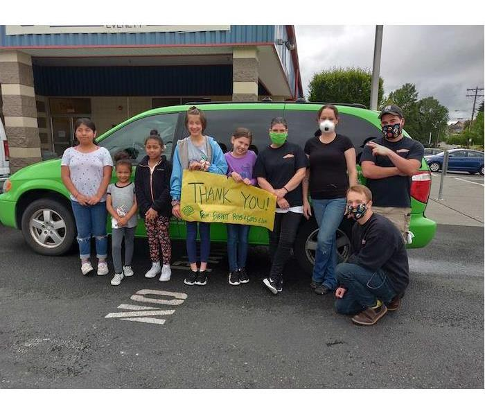 children and adults standing in front of a green SERVPRO van