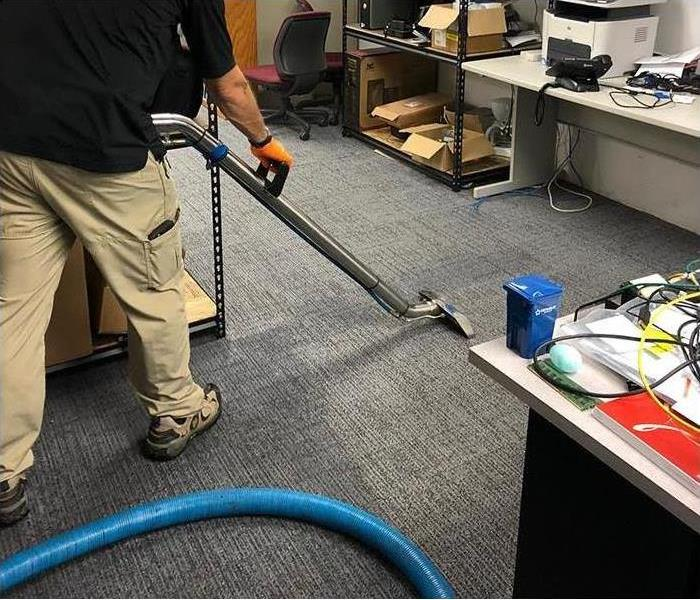 Technician using a water extraction equipment on the carpet in a home