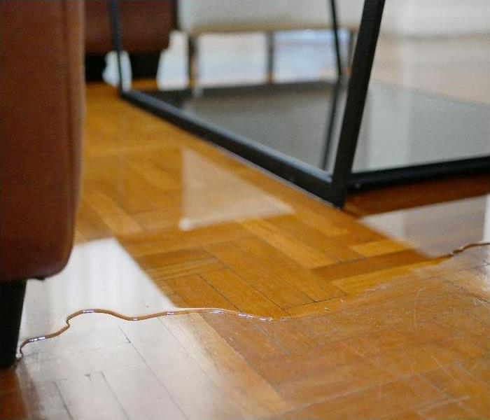 water flooding on living room parquet floor in a house